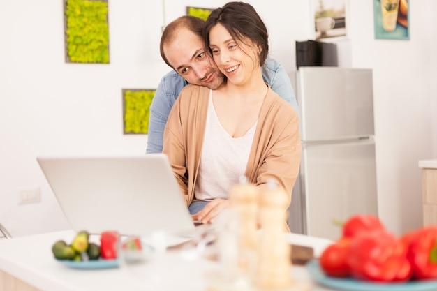 식탁에 건강한 야채와 함께 부엌에서 노트북을 사용하는 웃는 커플. 현대적인 wi-fi 무선 인터넷 기술을 사용하여 집에서 사랑하는 부부의 행복한 사랑의 쾌활한 낭만적인