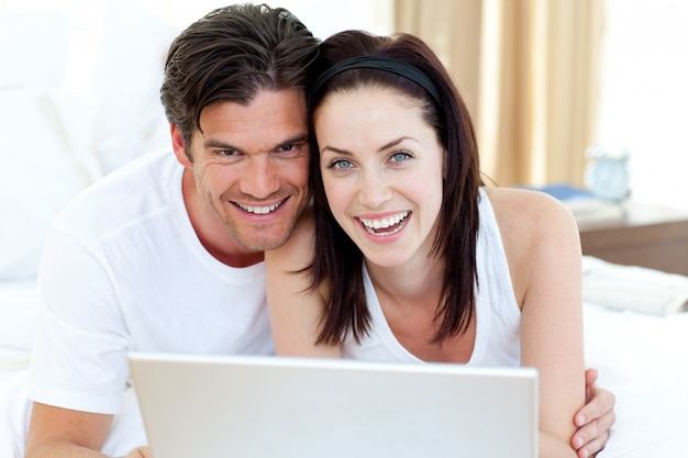 Smiling couple using a laptop lying on their bed