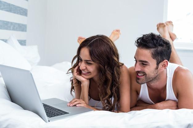 Smiling couple using laptop while lying under blanket