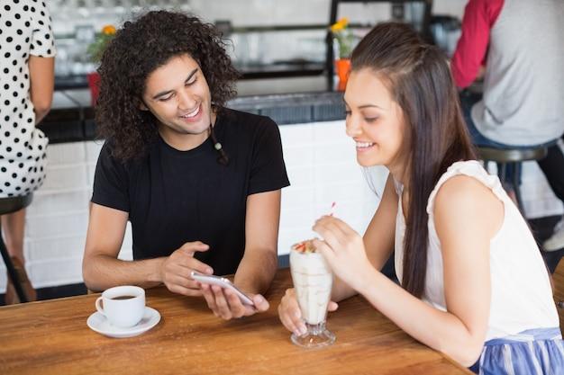 レストランでドリンクを飲みながら携帯電話を使用して笑顔のカップル