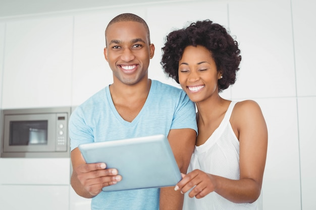 Smiling couple using tablet in the kitchen