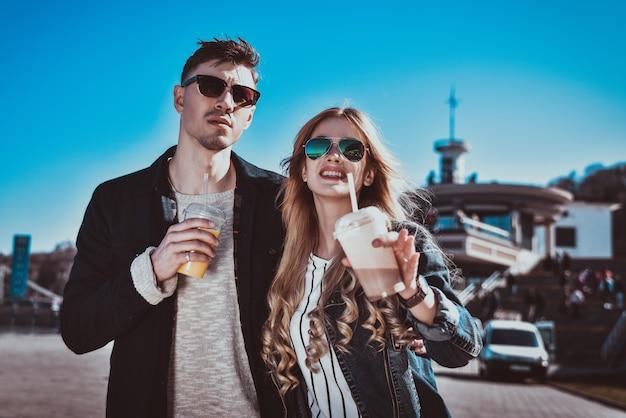 笑顔のカップルが週末に通りを歩き、カクテルを飲みます