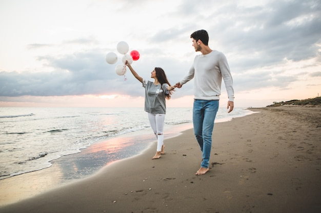 Smiling couple walking on the beach with balloons