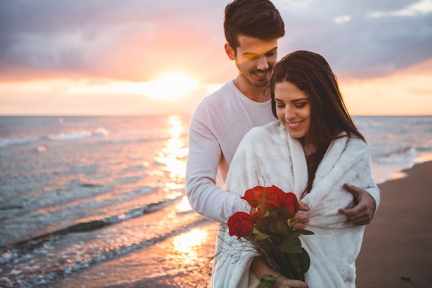Smiling couple walking on the beach with a bouquet of roses at sunset