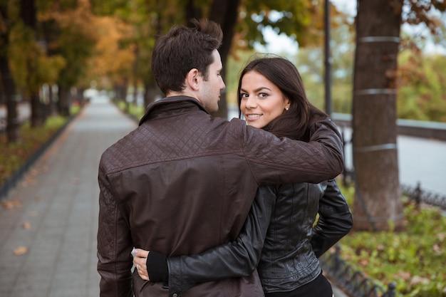 屋外を歩いて、正面を振り返って笑顔のカップル