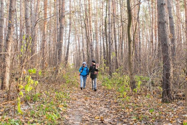 가 자연 배경 위에 배낭과 함께 걷고 웃는 커플.