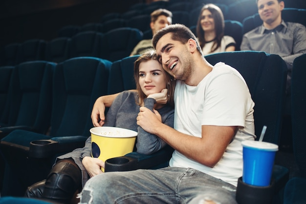 Smiling couple watching comedy movie in cinema. showtime, entertainment industry