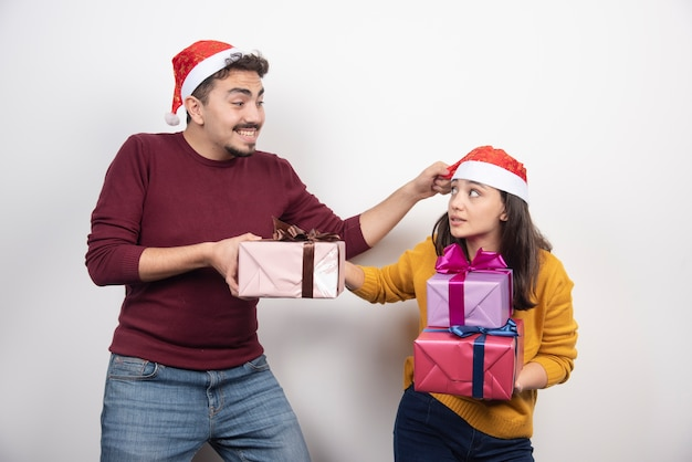 Smiling couple in winter fashion holding presents on white background.