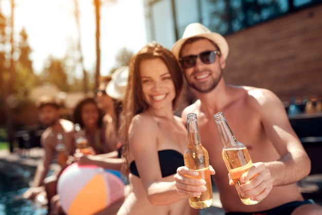 Smiling couple with alcoholic drinks at poolside