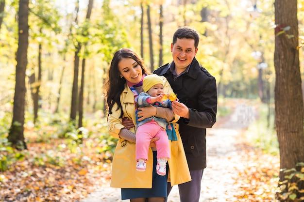 Улыбающаяся пара с ребенком в осеннем парке