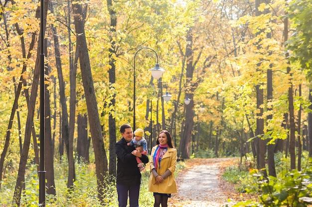 Улыбающаяся пара с ребенком в парке