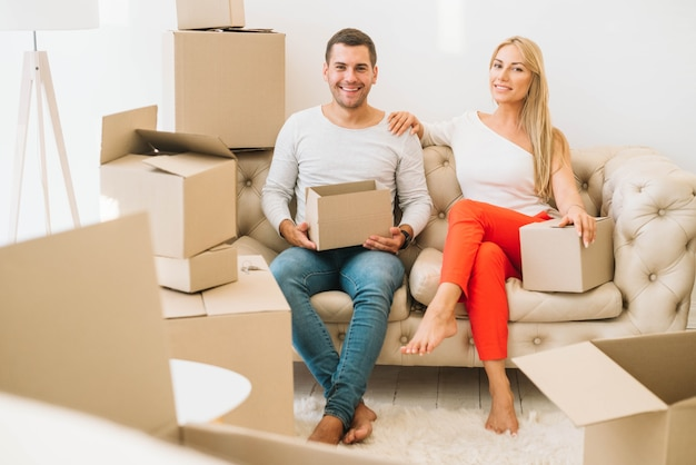 Smiling couple with cardboard boxes