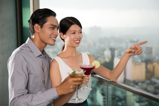 Smiling couple with cocktails standing on balcony