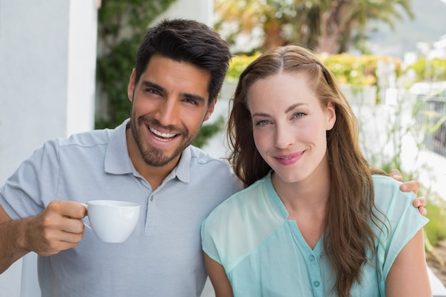 Smiling couple with coffee cup at cafã©