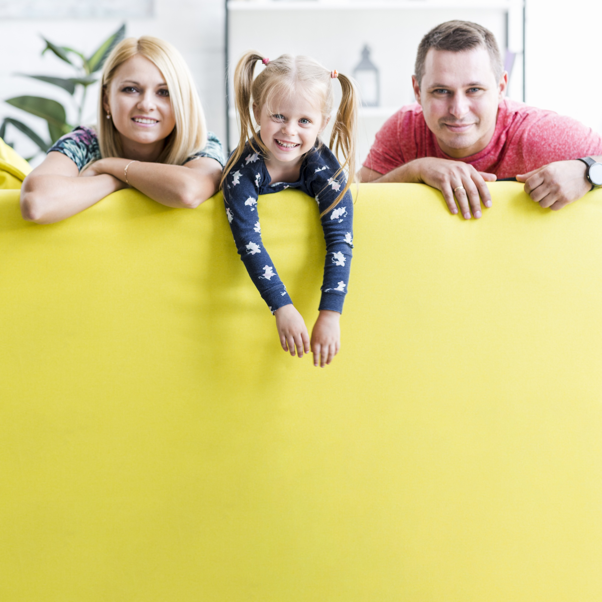 Smiling couple with kid sitting on sofa