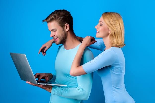 Улыбаясь пара с ноутбуком. счастливая пара с персональным компьютером. мужчина держит ноутбук. современные технологии и коммуникации. стильная пара. счастливая семья. ищу. онлайн покупки. интернет магазин. изолированный.