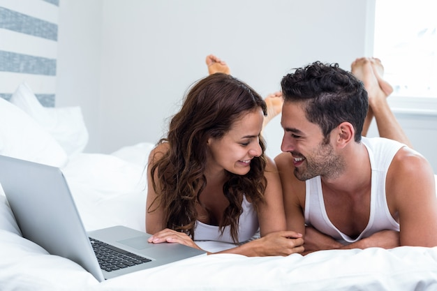 Smiling couple with laptop while lying under blanket