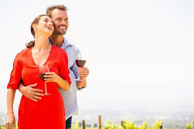 Smiling couple with red wine looking away