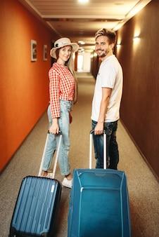 ホテルの廊下でスーツケースと笑顔のカップル