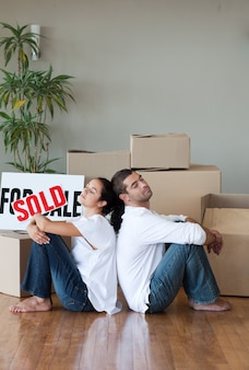 Smiling couple with unpacking boxes moving to a new house