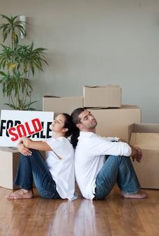 新しい家に移動するボックスを開けて笑うカップル