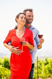 Smiling couple with wineglasses looking away