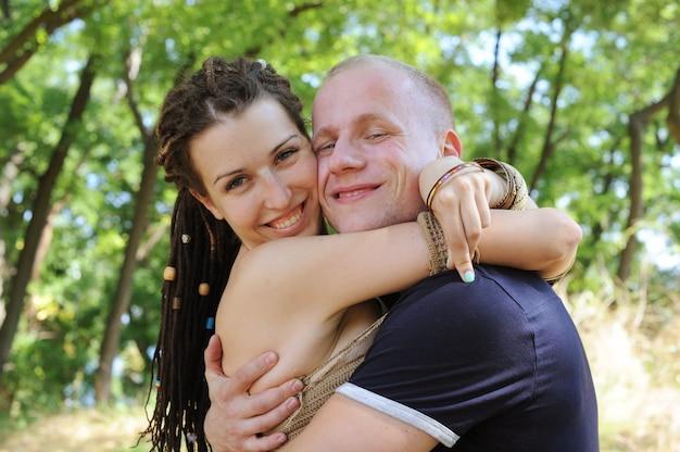 Улыбающаяся пара, женщина, обнимающая мужчину, на открытом воздухе в парке