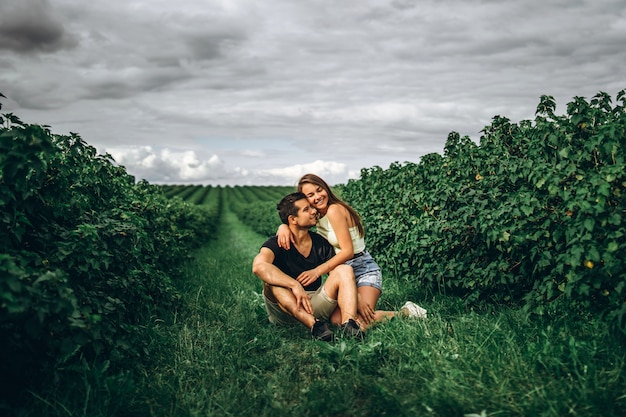 A smiling couple, woman with long hair and man sitting between currant bushes and hugging.