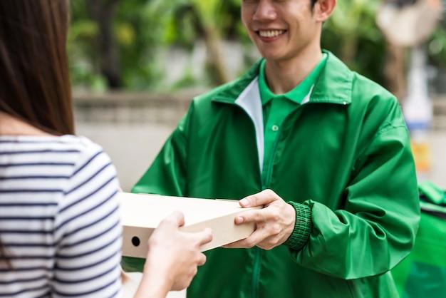 야외에서 여자 피자 상자를주는 택배 배달원 미소