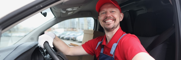 Smiling courier driver sits behind wheel of car