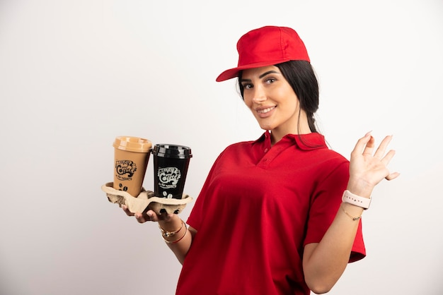 Улыбающийся курьер в униформе, разносит кофе на вынос. фото высокого качества