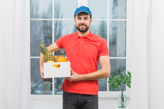 Smiling courier with box of fruits