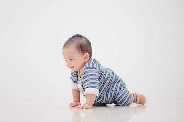 自宅の床にクロールアジアの男の子の笑顔