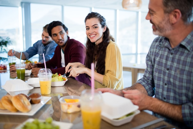 Smiling creative business team having meal in office