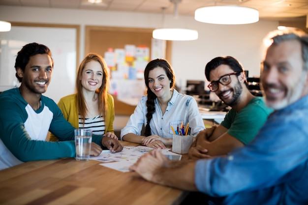 Улыбаясь творческой деловой команды, сидя за столом в офисе