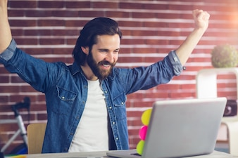 Smiling creative businessman with arms raised looking at laptop