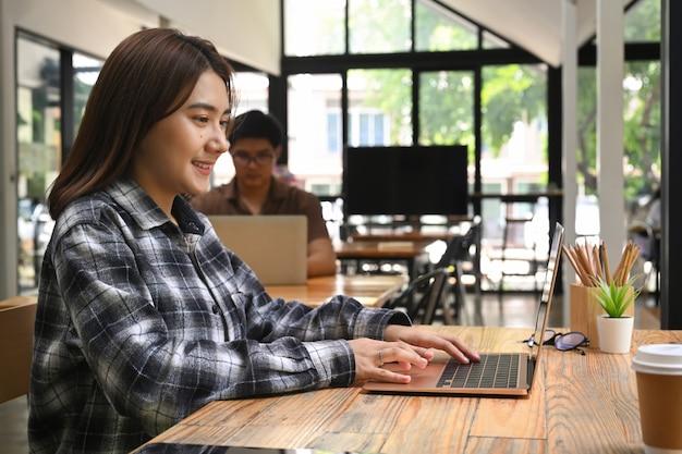 Улыбается творческая женщина, работающая с ноутбуком в офисе.