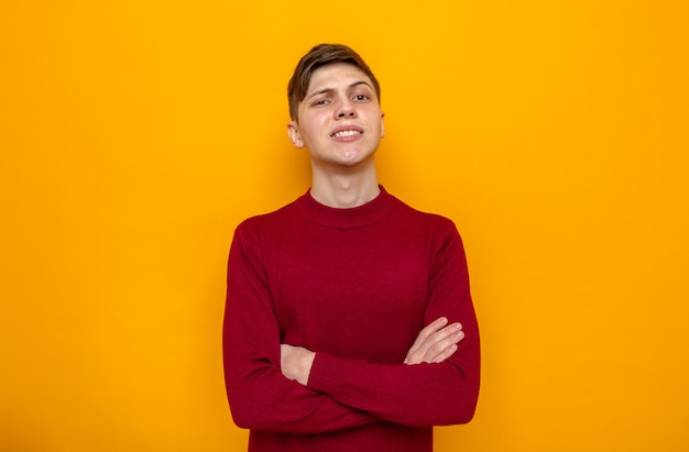Sorridente mani incrociate giovane bel ragazzo che indossa un maglione rosso