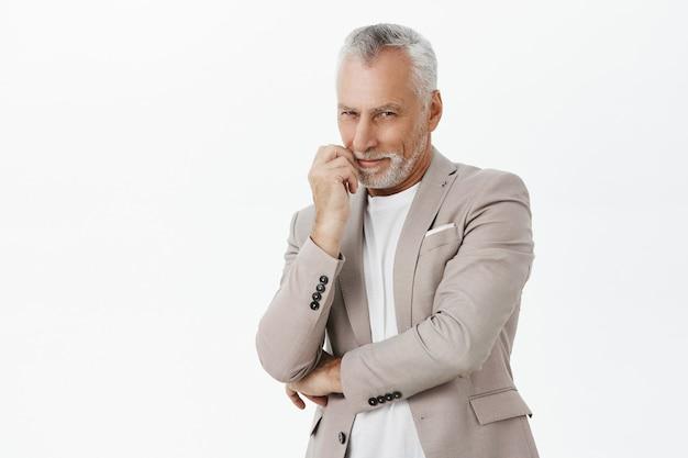 白い背景の上に興味をそそられ、喜んで見えるスーツの狡猾な年配の男性の笑顔