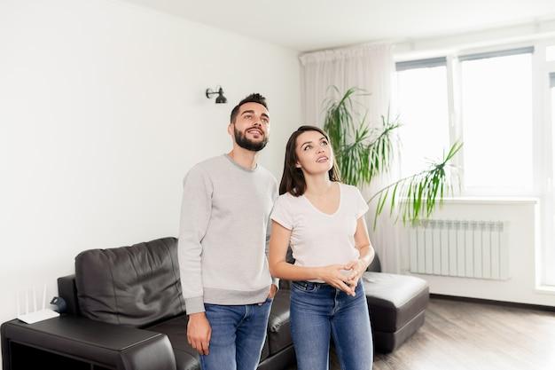 Улыбающаяся любопытная молодая пара в повседневных нарядах стоит в комнате с современной мебелью и рассматривает квартиру в аренду