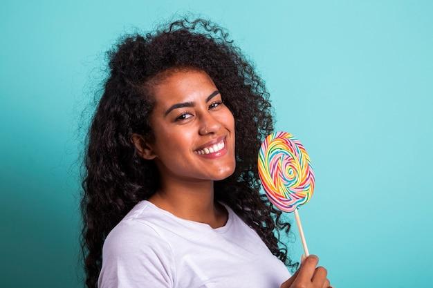 사탕 막대 사탕을 들고 밝은 흰색 티셔츠에 곱슬 아프리카 소녀 미소. 롤리팝으로 앞 얼굴을 숨기고 젊은 명랑 한 여자