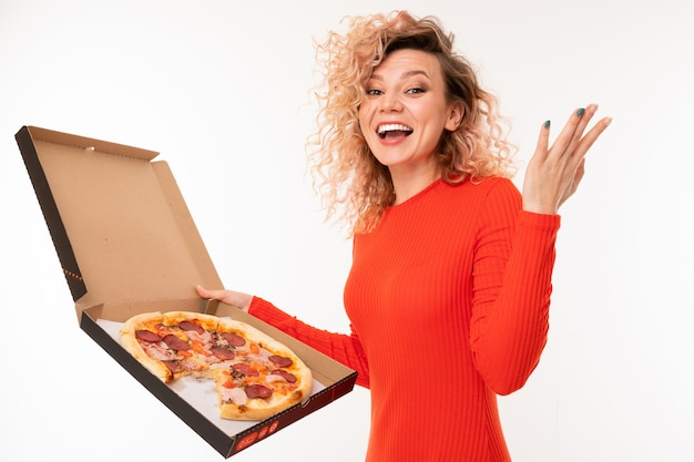 Smiling curly blond girl in a red dress holds a box of pizza on white wall