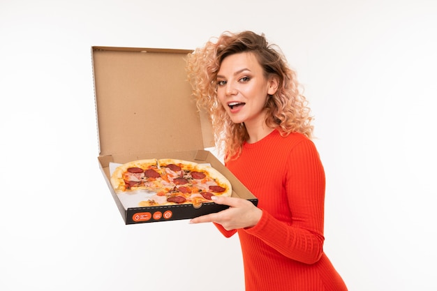 Smiling curly blond girl in a red dress holds a box of pizza on white