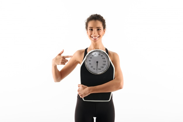 Smiling curly brunette fitness woman holding weighting scales