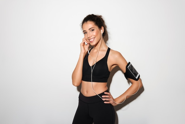 Smiling curly brunette fitness woman listening music by smartphone