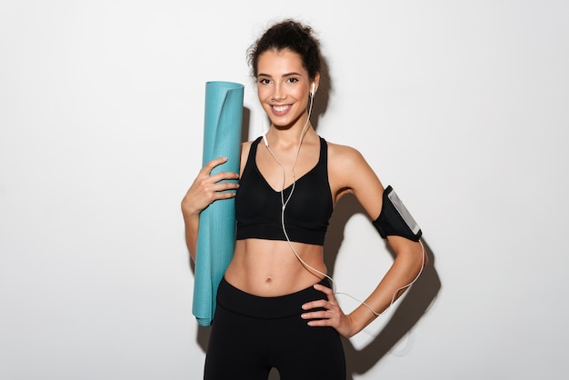 Smiling curly brunette sports woman holding fitness mat