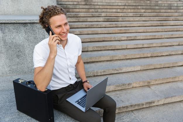 Улыбающийся кудрявый деловой человек с портфелем и портативным компьютером разговаривает со смартфоном, сидя у лестницы