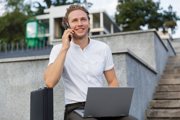 Улыбающийся кудрявый деловой человек с портфелем и портативным компьютером во время разговора по смартфону и сидя у лестницы