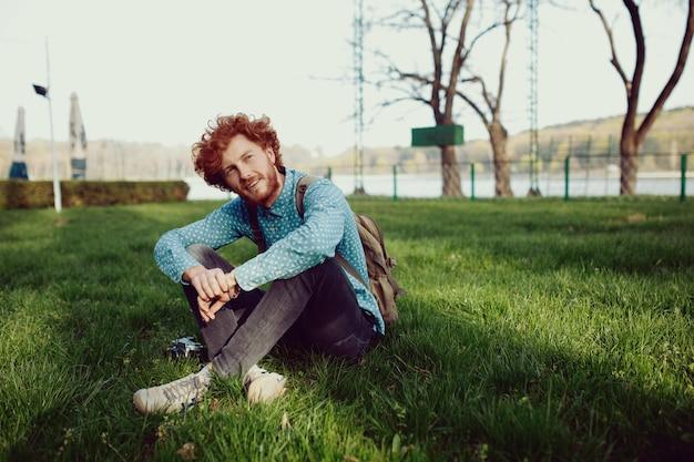 Улыбающийся кудрявый рыжий мужчина отдыхает на траве скрещенными ногами