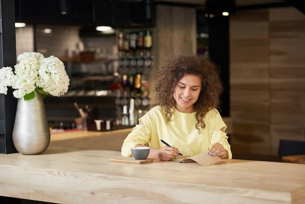 Smiling curly girl writing in blocknote drinking coffee, sitting in restaurant.